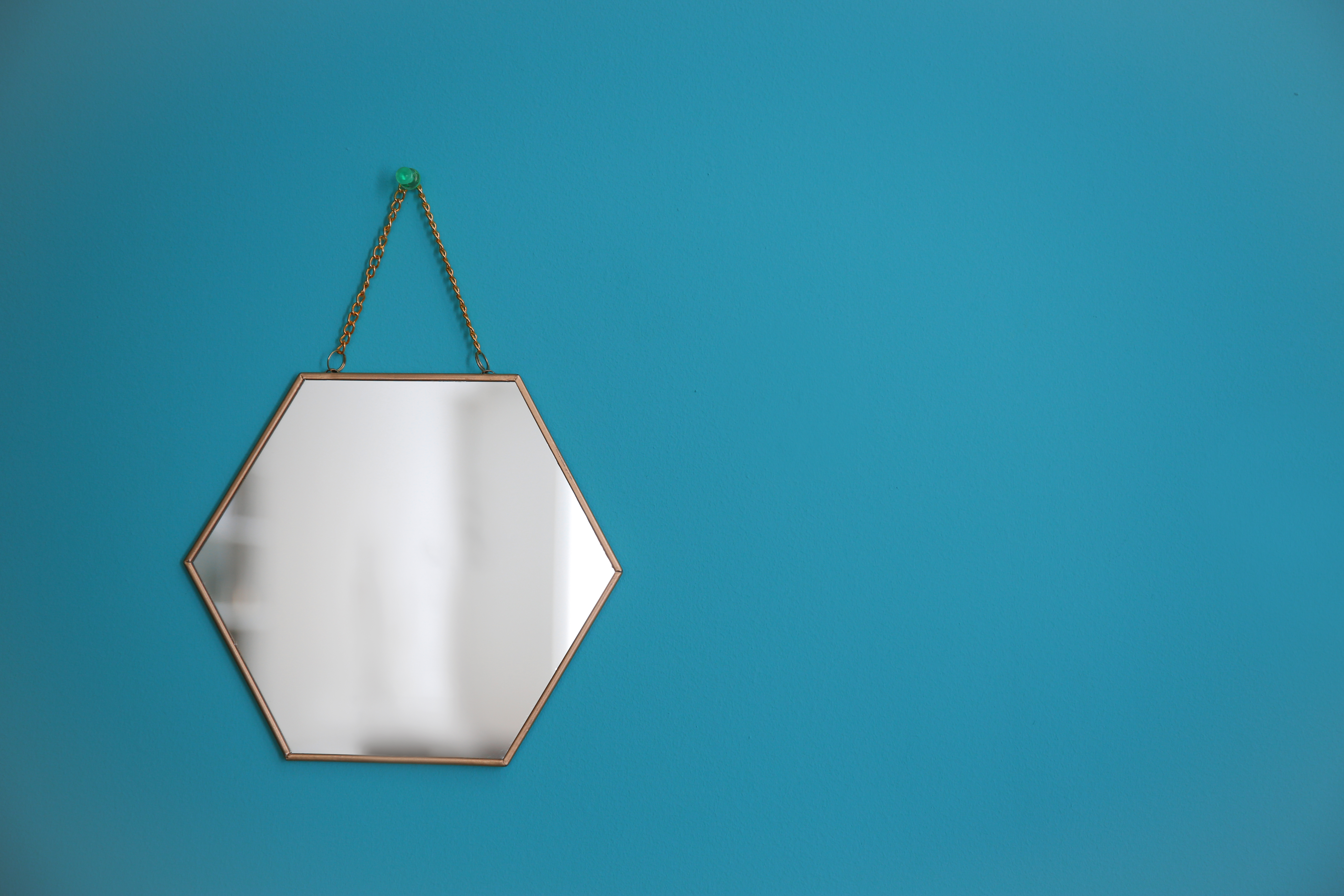 Mirror hanging on empty color wall
