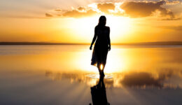 Young woman walking on water at sunset